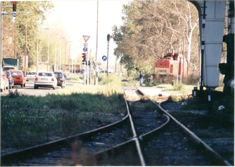 és tényleg! Pont ugyanezen a kapun halad ki egy Dacia 1998-ban. A Szerémi út ekkor már megvan, ezt 1995-ben építették ki az újbudai tehermentesítő út részeként, az iparvágányokat részben keresztezve, részben felszámolva. A képen látható gépmenet érdekessége, hogy az iparvágány-hálózatot 1997. december 31-én hivatalosan üzemen kívül helyezték, de az Épületelemgyár ezután is ragaszkodott a vasúti kiszolgáláshoz, így ritkán továbbra is jártak vonatok ebbe az irányba, mígnem 2000 körül a MÁV véglegesen felmondta a szállítási szerződést. Ma már csak a gyárak belső területein találkozhatunk sínekkel, így például a táborainkból újbudai falmászóhely udvarán. Az alsó képen a volt Keksz- és Ostyagyár területén lévő fordítókorongot láthatjuk 2006-os állapotában. (Kép és információk: http://villamosok.hu/balazs/bpvasut/ipvg/andor/index.html)
